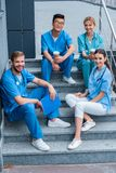Smiling multicultural medical students sitting on stairs and looking. At camera stock photography
