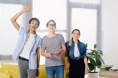 Smiling multicultural teenagers greeting someone. At home stock photos