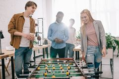 smiling multiethnic businesspeople going to play table football in modern stock photos