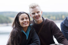 Smiling Multiethnic Couple At Lakeside Camping. Portrait of smiling multiethnic couple enjoying camping at lakeside royalty free stock images