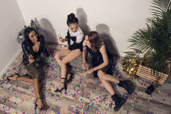 Smiling multiethnic girls sitting and drinking champagne at party. Young smiling multiethnic girls sitting and drinking champagne at party Stock Images