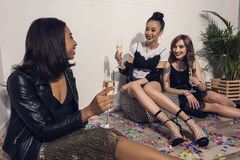 Smiling multiethnic girls sitting and drinking champagne at party. Young smiling multiethnic girls sitting and drinking champagne at party Stock Image