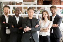 Smiling diverse team posing with arms crossed royalty free stock images