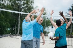 smiling multiethnic old volleyball players giving high five to each other royalty free stock images