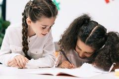 Smiling multiethnic schoolgirls studying together in classroom Stock Photos
