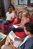 Multiethnic students studying together. Smiling multiethnic students with books studying together at home Stock Photography
