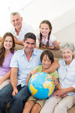 Smiling multigeneration family with globe Stock Photo