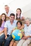 Smiling multigeneration family with globe Stock Photo