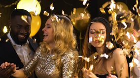Smiling multiracial couples dancing at party under falling confetti, happiness