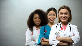Smiling multiracial doctors with red ribbons, international AIDS awareness sign royalty free stock photos