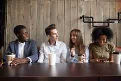 Smiling multiracial friends drinking coffee having fun in cafe. Happy multiracial friends talking and using phones during meeting in coffeeshop, smiling stock photos