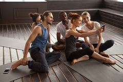 Smiling multiracial people making selfie on smartphone at yoga t royalty free stock photos