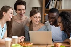 Smiling multiracial people using laptop together, having fun. Smiling multiracial people using laptop together, watching online movie or video in social network royalty free stock image