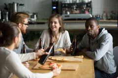 Smiling multiracial young friends talking drinking beer eating p royalty free stock image