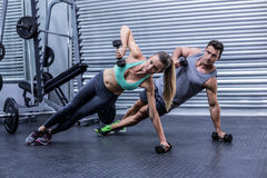 Smiling muscular couple doing side plank. Portrait of a muscular couple doing side plank while lifting weights Stock Photo