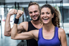 Smiling muscular couple flexing biceps Royalty Free Stock Image