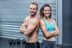 Smiling muscular couple giving back to back Royalty Free Stock Images
