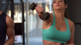 Smiling muscular couple lifting dumbbells. In crossfit stock video footage
