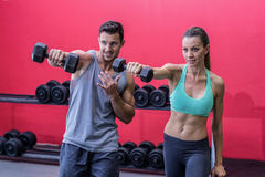 Smiling muscular couple lifting dumbbells. Muscular couple lifting dumbbells at the crossfit gym Royalty Free Stock Photo