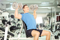 Smiling muscular guy lifting weights in gym club. Smiling muscular guy lifting weights in a gym Royalty Free Stock Photos