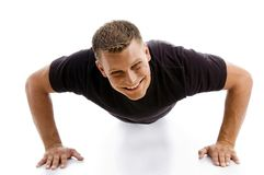 Smiling muscular male doing push ups Stock Images