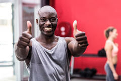 Smiling muscular man gesturing thumbs up Stock Photo