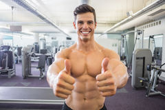 Smiling muscular man giving thumbs up in gym Royalty Free Stock Images