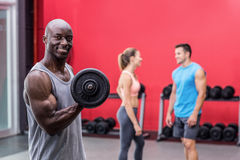 Smiling muscular man lifting a dumbbell Royalty Free Stock Image