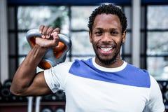 Smiling muscular man lifting kettlebells Stock Photo
