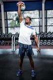 Smiling muscular man lifting kettlebells Royalty Free Stock Image