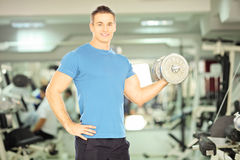 Smiling muscular man lifting weight in fitness club Royalty Free Stock Photo
