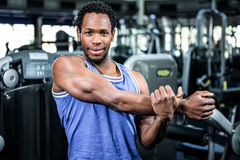 Smiling muscular man stretching arms Royalty Free Stock Image
