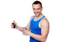 Smiling muscular sportsman with expanders Royalty Free Stock Photos