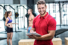 Smiling muscular trainer writing on clipboard Stock Photos