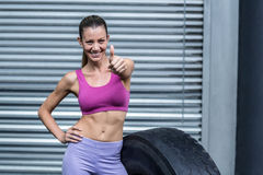 Smiling muscular woman gesturing thumbs up Stock Photos