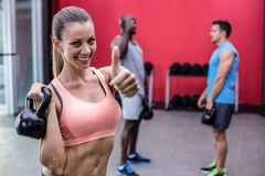 Smiling muscular woman lifting a kettle bell stock images