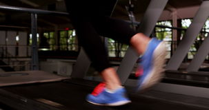 Smiling muscular woman running on treadmill. In crossfit stock video