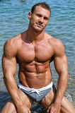 Smiling, muscular young bodybuilder shirtless on his knees Royalty Free Stock Photo