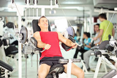 Smiling muscular young man exercising in a club Royalty Free Stock Photos