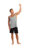 Smiling Muscular Young Man Pointing Up Stock Photography