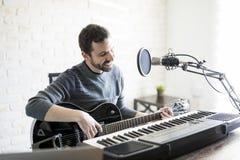 Smiling musician playing music on radio. Handsome hispanic man enjoying playing guitar at radio station, playing music live on air and smiling Royalty Free Stock Photo
