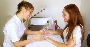 Smiling nail technician examining pretty customers hands stock video