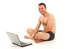Smiling naked man working on laptop Stock Photo