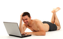 Smiling naked man working on laptop Royalty Free Stock Images