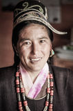Smiling native woman in Arunachal Pradesh. Dorjeling, Arunachal Pradesh - circa March 2012: Native woman with traditional hat and necklace made of beads smiles Stock Photo