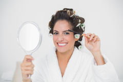 Smiling natural brunette using eyebrow brush Royalty Free Stock Images