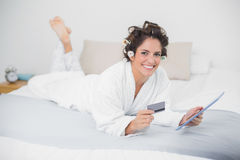 Smiling natural brunette using tablet and credit card Stock Images