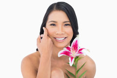 Smiling natural model posing with lily and caressing her face Royalty Free Stock Image