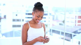 Smiling natural model sending a text message Royalty Free Stock Image