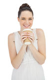 Smiling natural model in white dress drinking coffee Stock Photo